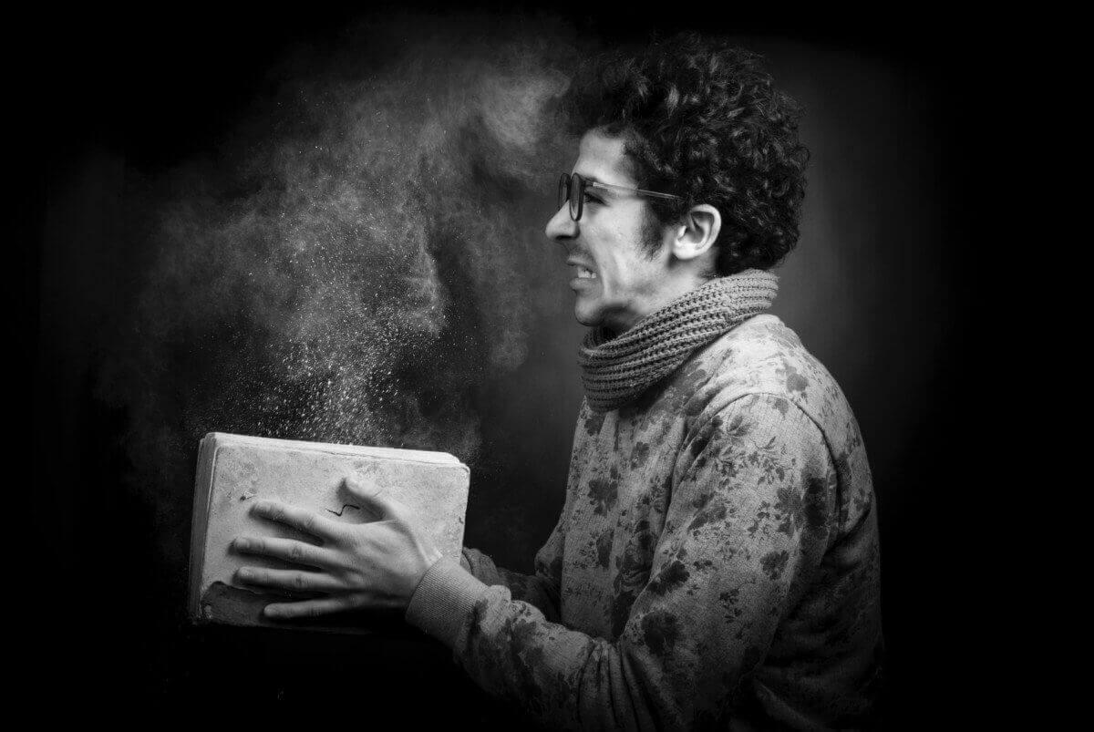 Uomo che chiude un libro polveroso.